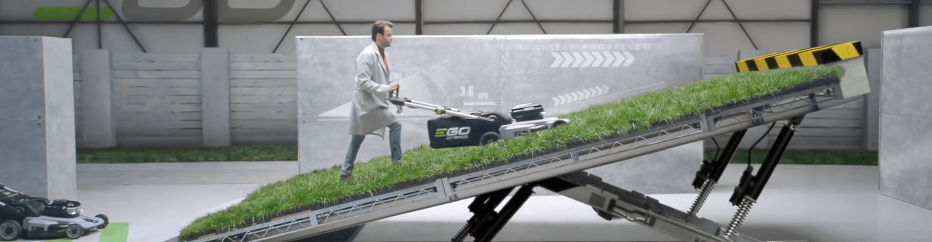 A man in a lab environment testing an EGO Mower on a steep incline.