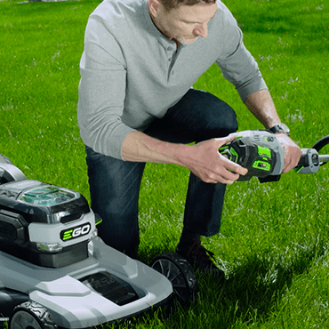 Man swapping EGO battery from EGO lawn mower to  EGO string trimmer.